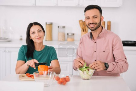 Photo for Happy couple looking at camera while sitting at kitchen table and preparing salad together - Royalty Free Image