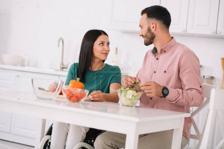 Photo for Happy disabled woman looking at smiling boyfriend while preparing salad together - Royalty Free Image