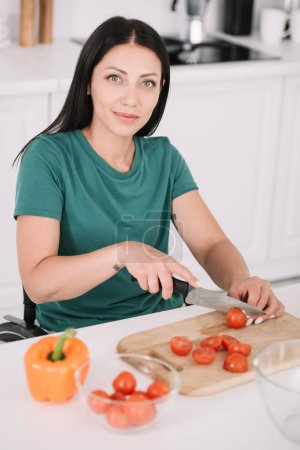 Photo for Beautiful disabled woman cutting tomatoes while looking at camera - Royalty Free Image
