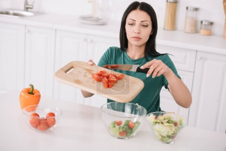 Photo for Attractive young woman holding chopping board while adding sliced tomatoes in glass bowl - Royalty Free Image