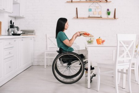 Photo for Side view of disabled young woman preparing salad while sitting on wheelchair near table - Royalty Free Image