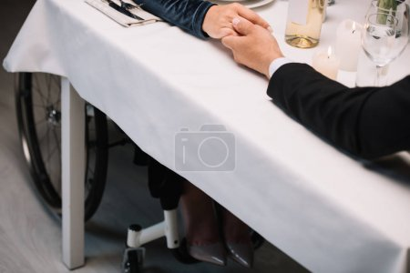 Photo for Cropped view of disabled woman holding hands with boyfriend while having romantc dinner - Royalty Free Image