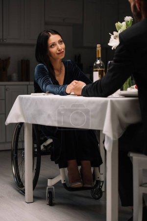 Photo pour Vue recadrée de l'homme retenant des mains avec la petite amie handicapée pendant le dîner romantique - image libre de droit