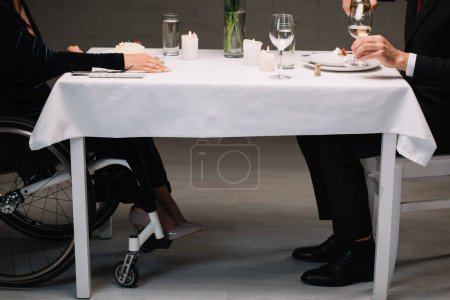Photo pour Vue recadrée de femme handicapée dans le fauteuil roulant ayant le dîner romantique avec le petit ami - image libre de droit