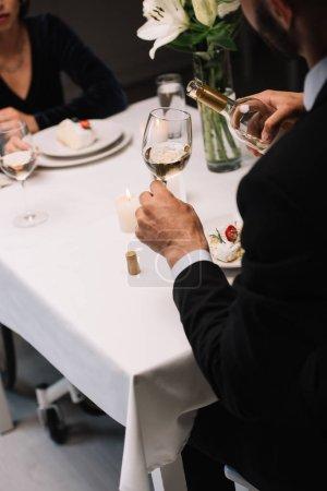 Photo pour Vue recadrée de l'homme versant le vin blanc dans le verre tout en ayant le dîner romantique avec la petite amie handicapée - image libre de droit