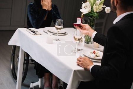Photo pour Vue recadrée de l'homme faisant la proposition de mariage à la petite amie handicapée pendant le dîner romantique - image libre de droit