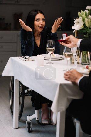 Photo pour Vue recadrée de l'homme faisant la proposition de mariage à l'ami handicapé heureux et étonné pendant la soirée romantique - image libre de droit