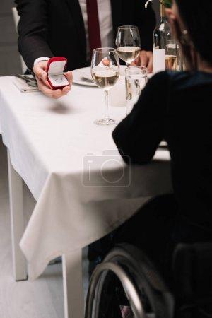 Photo pour Vue partielle du petit ami faisant la proposition de mariage à la jeune femme handicapée tout en ayant le dîner romantique - image libre de droit