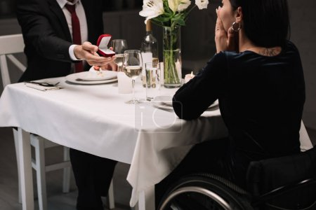 cropped view of young man making wedding proposal to disabled girlfriend while having romantic dinner