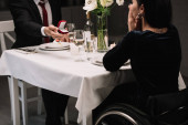 """Постер, картина, фотообои """"cropped view of young man making wedding proposal to disabled girlfriend while having romantic dinner"""""""
