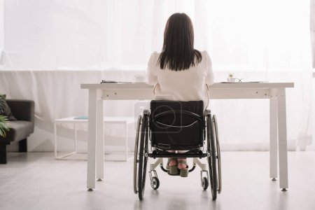 back view of businesswoman sitting in wheelchair near desk in office