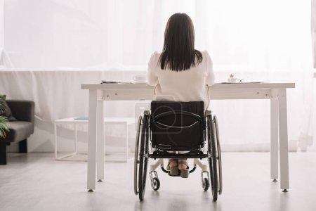 Foto de Vista trasera de la empresaria sentada en silla de ruedas cerca del escritorio en la oficina - Imagen libre de derechos