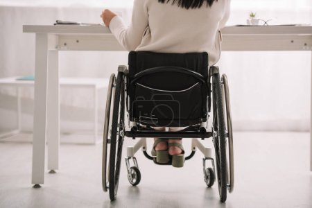Photo for Back view of disabled businesswoman sitting in wheelchair at workplace - Royalty Free Image