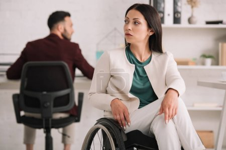 Photo for Serious disabled businesswoman looking away while sitting in wheelchair in office near colleague - Royalty Free Image