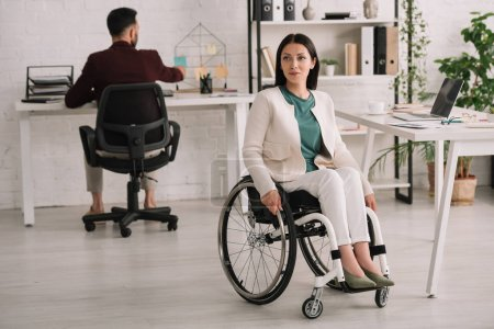 Photo for Attractive disabled businesswoman sitting in wheelchair in office near colleague - Royalty Free Image
