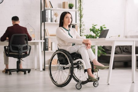 Photo for Serious disabled businesswoman sitting in wheelchair in office near colleague - Royalty Free Image