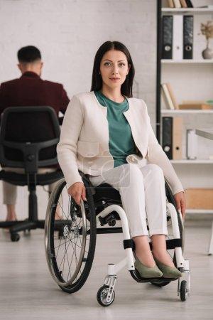 Photo pour Belle femme d'affaires handicapée souriant à l'appareil-photo tout en s'asseyant dans le fauteuil roulant près du collègue travaillant sur le fond - image libre de droit