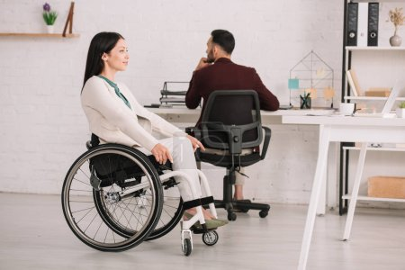 Photo for Smiling disabled businesswoman looking away while sitting in wheelchair near colleague - Royalty Free Image