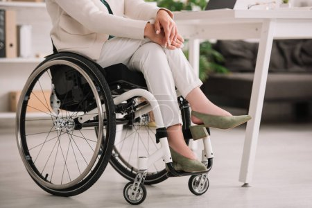 Photo for Cropped view of disabled businesswoman sitting in wheelchair with crossed legs - Royalty Free Image