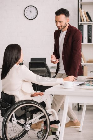 Photo for Smiling businessman holding smartphone while standing near disabled businesswoman in office - Royalty Free Image