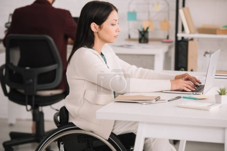 Photo for Disabled businesswoman typing on laptop while sitting at workplace in offce - Royalty Free Image