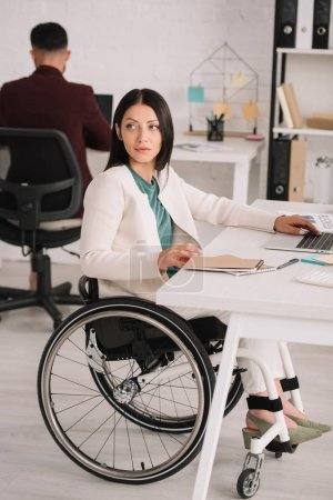 Photo for Attractive disabled businesswoman looking away while sitting in wheelchair at workplace near colleague on background - Royalty Free Image