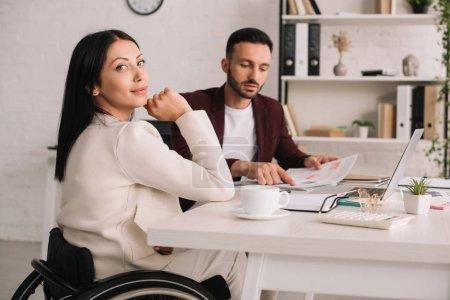 Foto de Atractiva mujer de negocios discapacitada sentada en el escritorio en la oficina cerca de colega guapo - Imagen libre de derechos