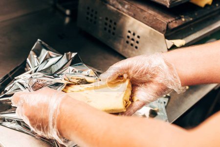 partial view of cook in gloves using aluminium foil while preparing doner kebab