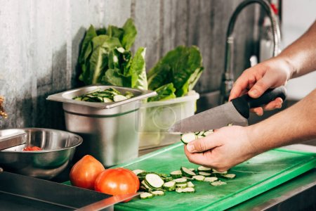 Photo for Cropped view of cook cutting cucumbers on chopping board - Royalty Free Image