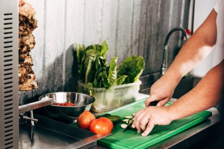 Photo for Cropped view of cook cutting vegetables at workplace - Royalty Free Image