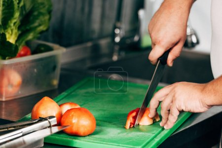 cropped view of cook cutting tomatoes on chopping board