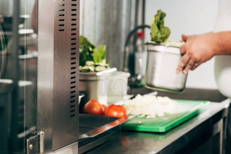 Photo for Cropped view of cook holding container in kitchen - Royalty Free Image