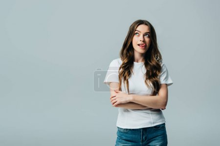 Photo for Beautiful girl in white t-shirt with crossed arms looking away isolated on grey - Royalty Free Image