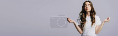 Photo for Beautiful girl in white t-shirt with closed eyes meditating isolated on grey, panoramic shot - Royalty Free Image