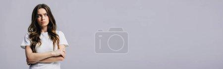 Foto de Triste hermosa chica en camiseta blanca con los brazos cruzados mirando lejos aislado en gris, tiro panorámico - Imagen libre de derechos