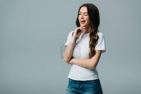 Photo pour Belle fille dans le clin d'œil blanc de t-shirt avec la bouche ouverte d'isolement sur le gris - image libre de droit