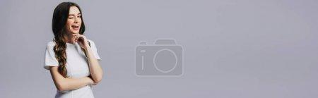 Photo pour Belle fille en blanc t-shirt clin d'oeil avec bouche ouverte isolé sur gris, vue panoramique - image libre de droit