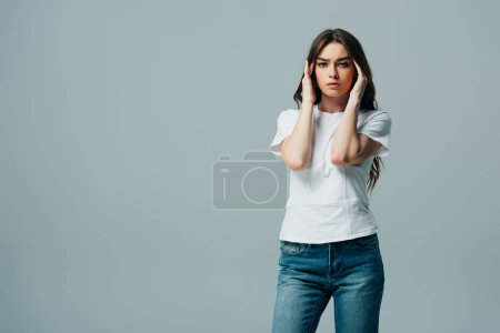 tense beautiful girl in white t-shirt suffering from migraine isolated on grey