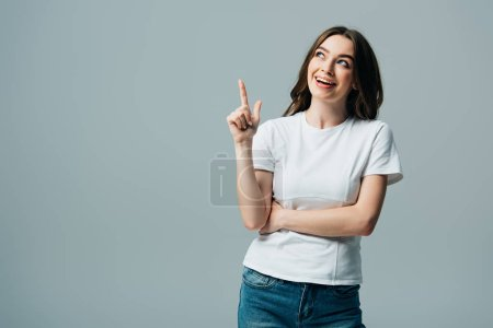 Photo for Happy beautiful girl in white t-shirt showing idea gesture and looking away isolated on grey - Royalty Free Image
