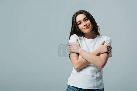 Photo pour Belle fille de sourire rêveuse dans le t-shirt blanc s'embrassant d'isolement sur le gris - image libre de droit