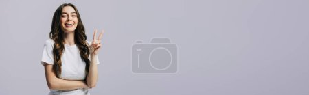Photo for Happy beautiful girl in white t-shirt showing peace sign isolated on grey, panoramic shot - Royalty Free Image