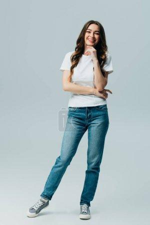 Photo pour Belle fille heureuse dans le t-shirt blanc et les jeans d'isolement sur le gris - image libre de droit