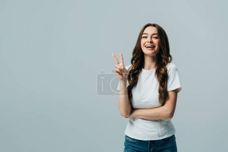 Photo for Happy beautiful girl in white t-shirt showing victory sign isolated on grey - Royalty Free Image