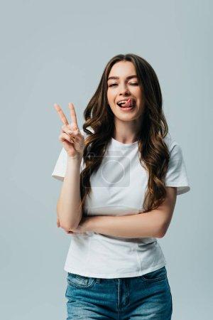 Photo pour Belle fille dans le t-shirt blanc affichant la langue et le signe de paix d'isolement sur le gris - image libre de droit