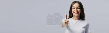 Photo pour Plan panoramique de belle fille heureuse en t-shirt blanc montrant pouce vers le haut isolé sur gris - image libre de droit