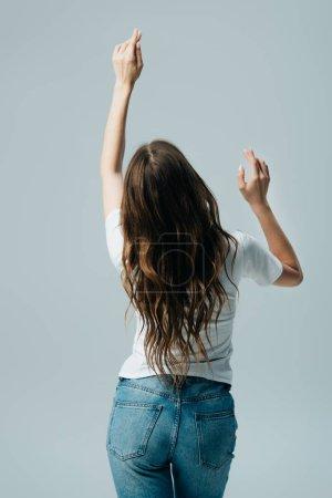 Foto de Vista trasera de la chica en camiseta blanca y jeans con el pelo largo bailando aislado en gris - Imagen libre de derechos