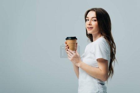 Photo pour Vue latérale de la belle fille souriante en t-shirt blanc avec tasse en papier isolé sur gris - image libre de droit