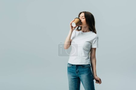 Photo for Beautiful girl in white t-shirt with closed eyes drinking from paper cup isolated on grey - Royalty Free Image