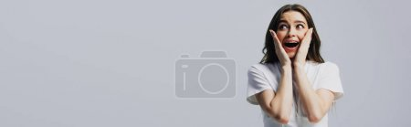 Photo pour Fille heureuse excitée touchant le visage d'isolement sur le gris, projectile panoramique - image libre de droit