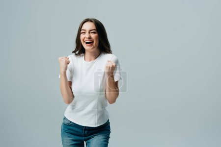 Photo for Excited happy beautiful girl in white t-shirt showing yes gesture isolated on grey - Royalty Free Image